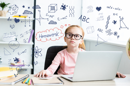 Thoughtful little schoolchild in eyeglasses looking up while sitting at desk and using laptop with learning icons