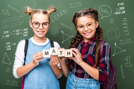 schoolchildren holding wooden cubes with word math near blackboard with mathematics symbols 写真素材