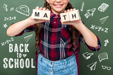 cropped image of schoolchild holding wooden cubes with word math near blackboard with back to school lettering