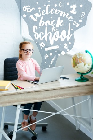 High angle view of child in eyeglasses smiling at camera while using laptop with icons and welcome back to school concept