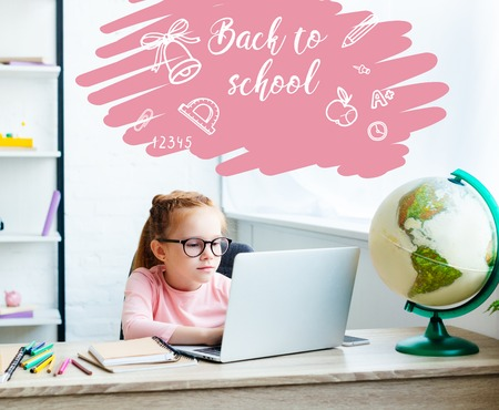 beautiful child in eyeglasses using laptop while studying at desk at home, with back to school lettering