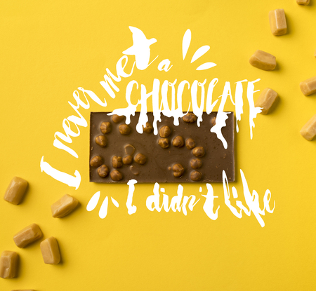 Top view of chocolate bar with scattered iris milk candies isolated on yellow with I never met a chocolate, I didnt like lettering