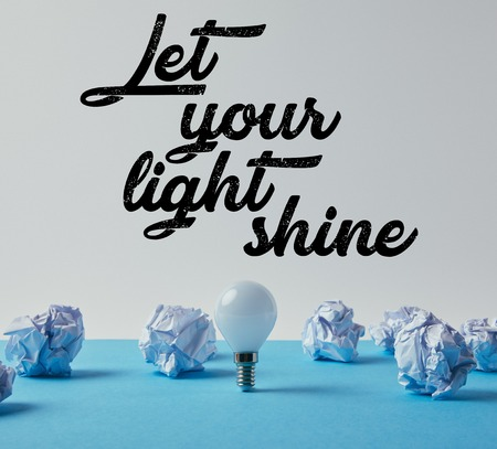 light bulb with crumpled papers on blue surface with let your light shine inspiration