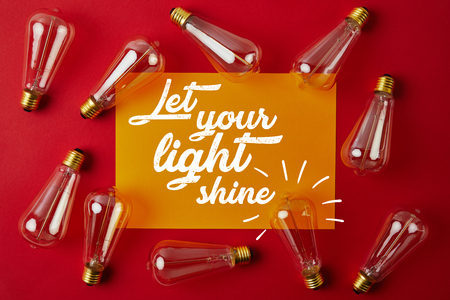 top view of vintage incandescent lamps on red surface with yellow paper and let your light shine inspiration