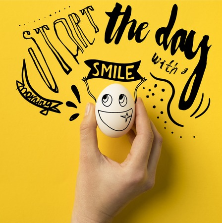 cropped image of woman holding egg isolated on yellow with Start the day with a smile inspiration Фото со стока