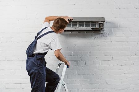 achteraanzicht van airconditioner reparateur staande op trapladder Stockfoto