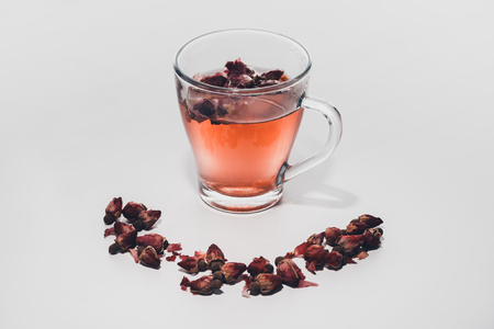 dried rose buds tea in cup on white tabletop