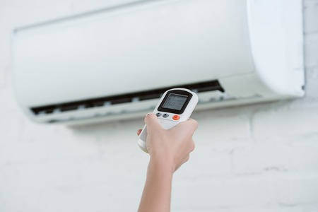 cropped shot of woman pointing at air conditioner hanging on brick wall with remote control Stock Photo