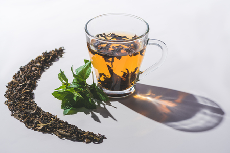 cup of black tea and mint on white tabletop
