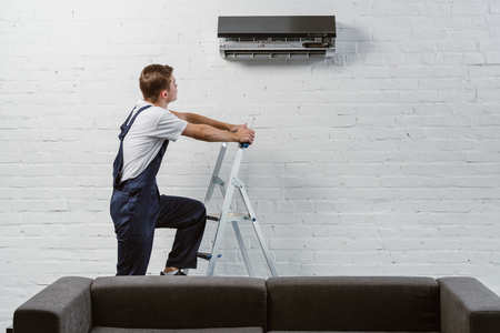 professional air conditioner repairman standing on stepladder
