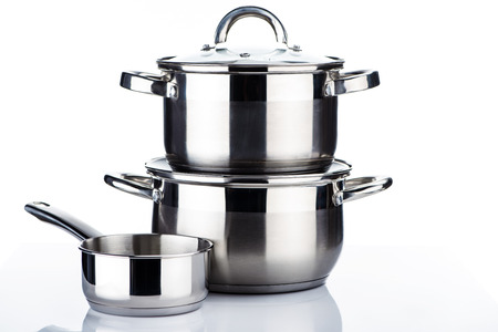 close-up view of shiny stainless steel pots and pans on white 스톡 콘텐츠