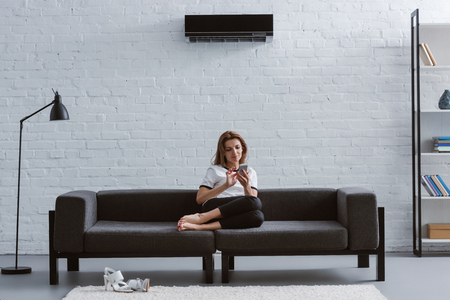 relaxed young woman using smartphone on sofa under air conditioner hanging on wall
