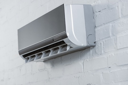 close-up shot of modern air conditioner hanging on white brick wall