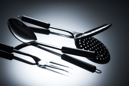 close-up view of colander, fork with two tines and ladle on grey 스톡 콘텐츠