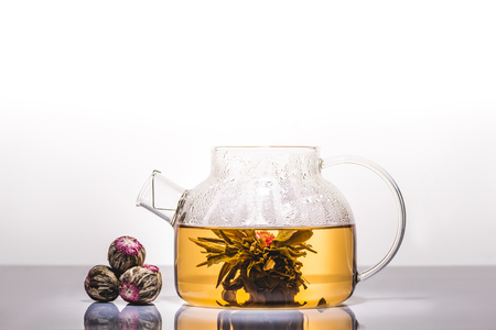 glass teapot of chinese flowering tea with tea balls on reflecting table
