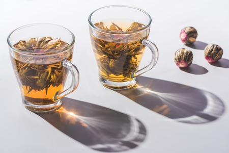 two cups of chinese flowering tea with tea balls on table