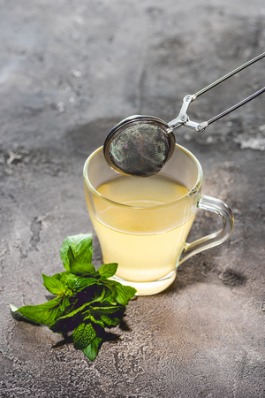 healthy tea with mint and tea strainer on grey surface