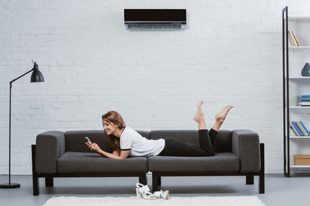 happy young woman using smartphone while lying on sofa under air conditioner hanging on wall 版權商用圖片