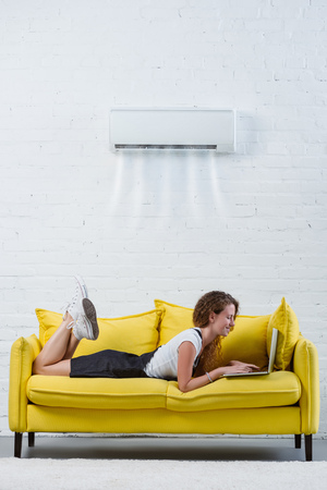 attractive young woman working with laptop on couch under air conditioner hanging on wall