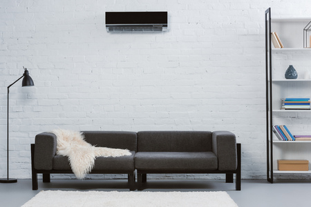 modern air conditioner hanging on white brick wall at living room Stockfoto