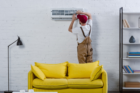 professional repairman fixing air conditioner hanging on white brick wall Stock Photo