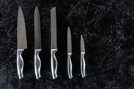 top view of different kitchen knives arranged on black marble surface with copy space Фото со стока