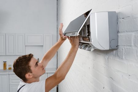repairman taking off dirty filter from air conditioner hanging on white brick wall Stock Photo
