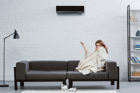 young woman covered with blanket on couch under air conditioner hanging on wall Stockfoto