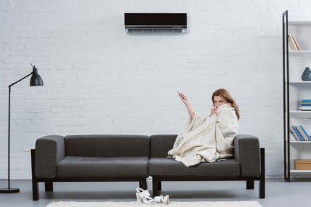 giovane donna coperta di coperta sul divano sotto il condizionatore d'aria appeso al muro