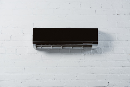 modern air conditioner hanging on white brick wall Stock fotó