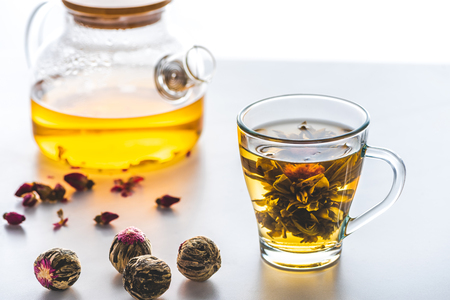 cup of chinese flowering tea with tea balls on white tabletop