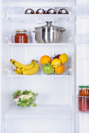 ripe fruits, salad, pan and preserved tomatoes in fridge