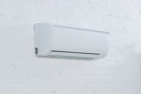 close-up shot of air conditioner hanging on brick wall