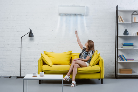 happy young woman pointing at air conditioner hanging on wall with remote control