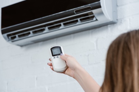 cropped shot of woman pointing at air conditioner with remote control