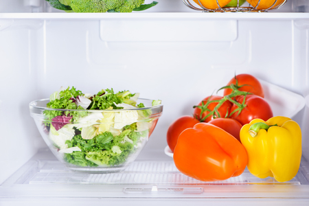 bowl of salad and ripe bell peppers in fridge Stock fotó