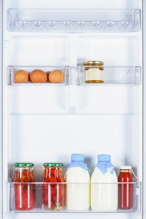 eggs, preserved tomatoes and bottles of milk in fridge Banco de Imagens - 108845749