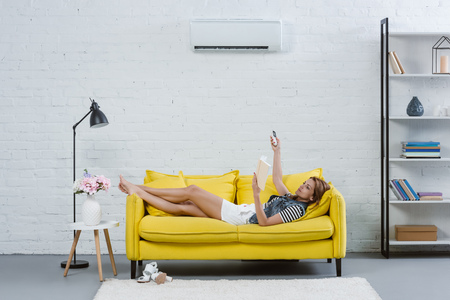 attractive young woman reading book on sofa and pointing at air conditioner with remote control Stockfoto