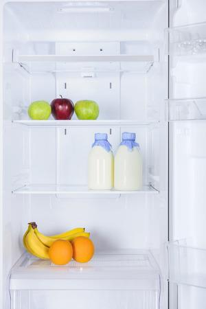ripe tasty apples, bananas, oranges and bottles of milk in fridge Stock fotó