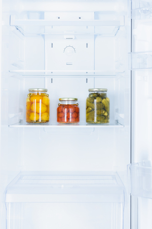 preserved vegetables in three glass jars in fridge Banco de Imagens - 108854123