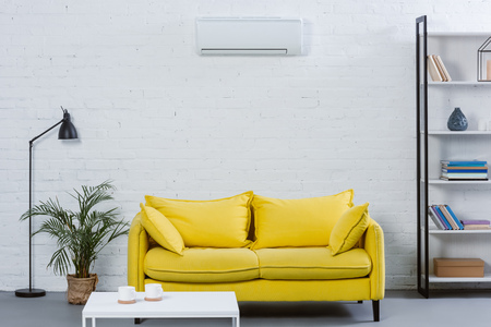 interior of modern living room with yellow couch and air conditioner hanging on white wall