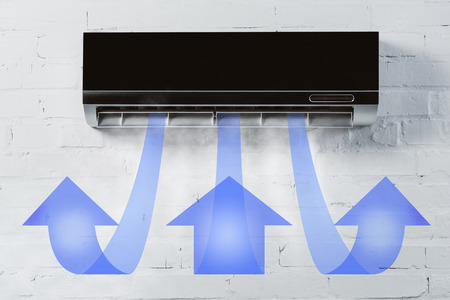 black air conditioner hanging on white brick wall and blowing air with arrows