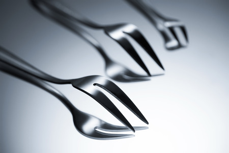close-up view of forks with two tines reflected on grey