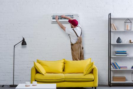Reparador profesional cambio de filtro para aire acondicionado colgado en la pared de ladrillo blanco.