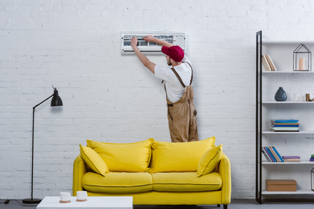 riparatore professionista cambiando filtro per condizionatore d'aria appeso al muro di mattoni bianchi