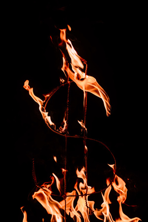 close up view of burning dollar sign isolated on black