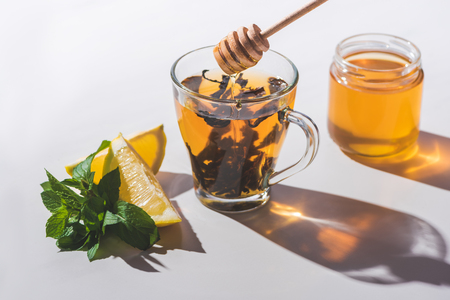 healthy tea with honey, lemon and mint on white tabletop Stok Fotoğraf