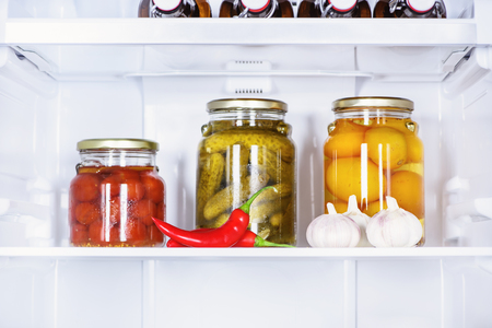 preserved vegetables in glass jars and ripe chili peppers in fridge