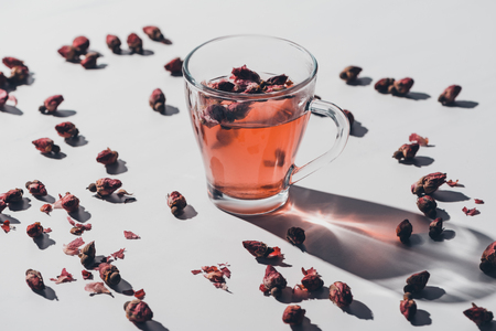 dried rose buds tea in cup and scattered roses on white tabletop