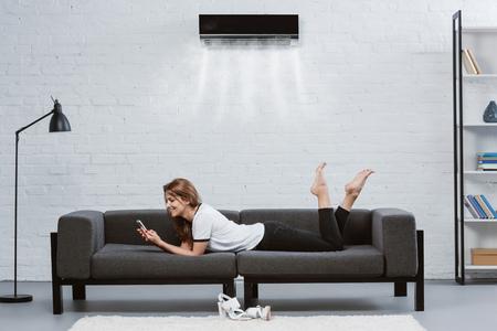 gelukkige jonge vrouw met behulp van smartphone op Bank onder airconditioner opknoping op muur
